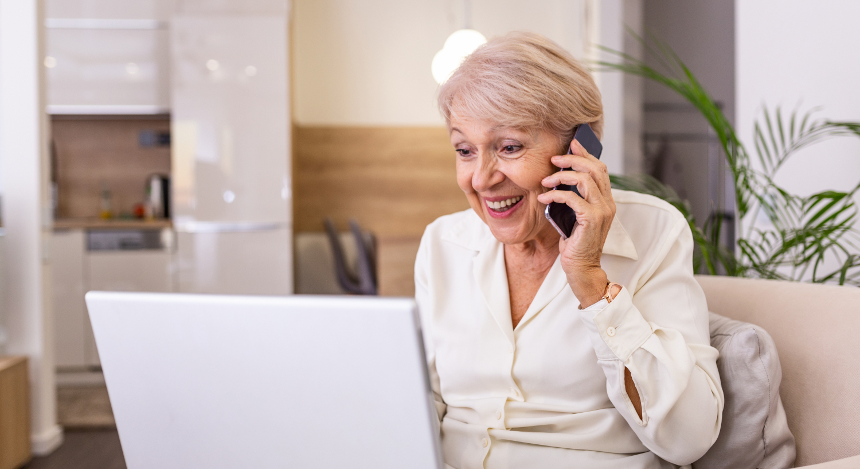 """Ältere Frau am Laptop mit Telefon: Für Das neue Beratungsangebot """"Treffpunkt Marktplatz digital"""" des Digitalen Engel von Deutschland sicher im Netz e.V."""