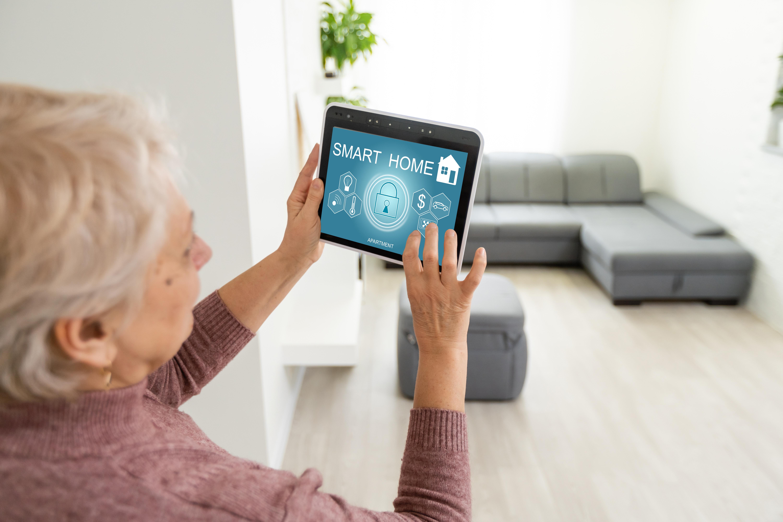 Ältere Frau nutzt Tablet für ihr Smart Home