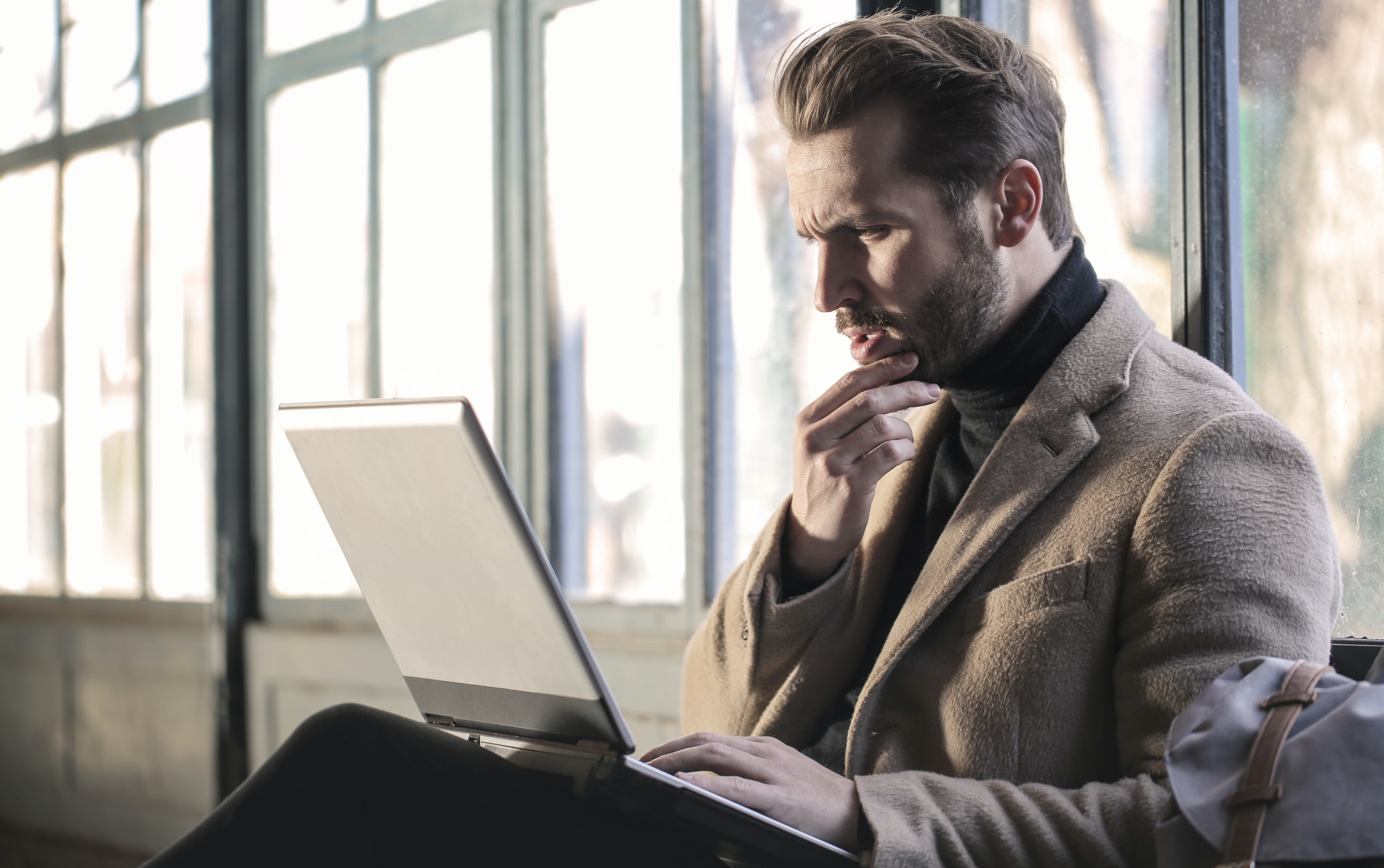 DsiN-Tipps: Bei Verschwörungstheorien richtig reagieren. Bildinhalt: Ein Mann sitzt mit skeptischem Gesichtsausdruck vor einem Laptop