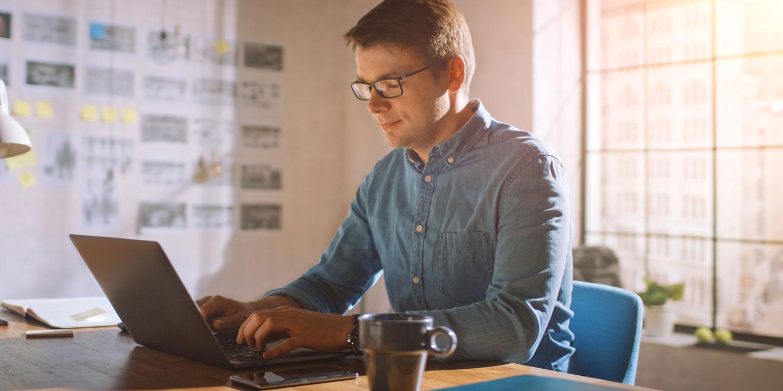 Ein Mann sitzt an einem Laptop im Homeoffice zum Thema Sichere IT trotz Homeoffice! Webinar der VdS Schadenverhütung