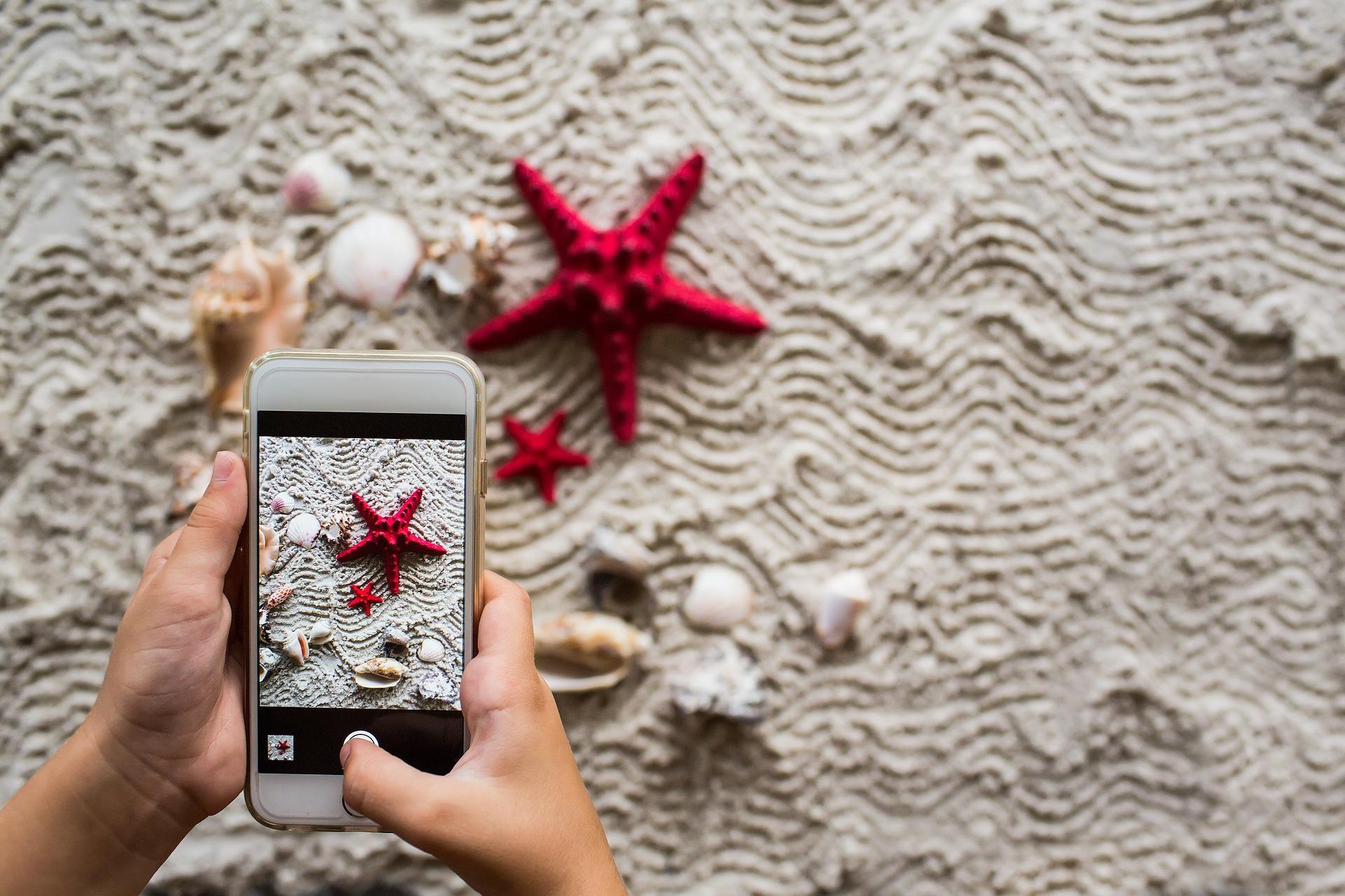 mit Smartphone wird Strandmotiv fotografiert