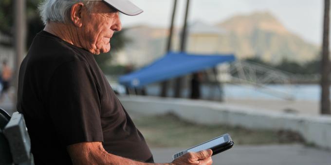 Älterer Mann sitzt auf einer Bank und liest ein E-Book