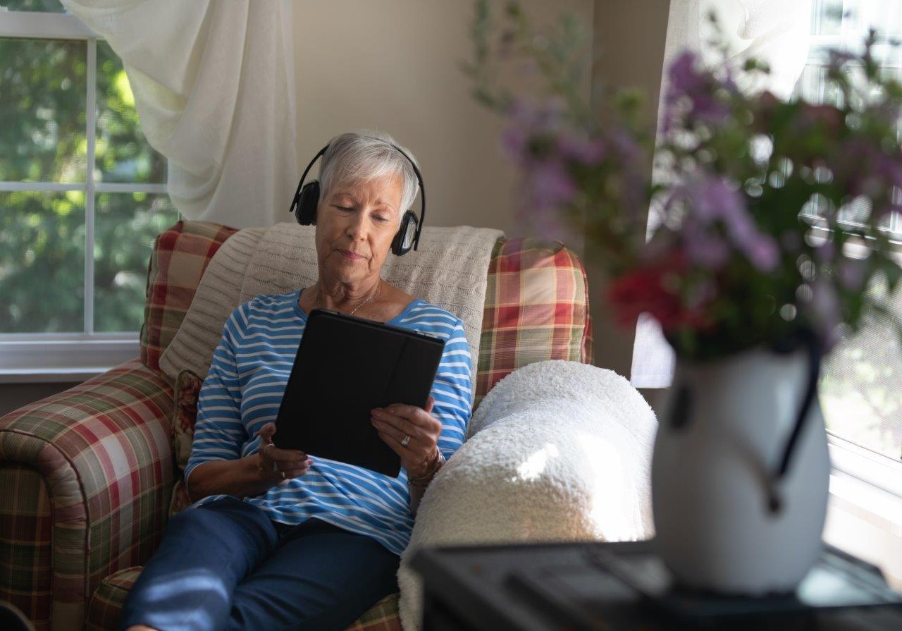 Ältere Frau sitzt im Sessel und benutzt Tablet und Kopfhörer, Quelle:  Shutterstock | Christine Glade