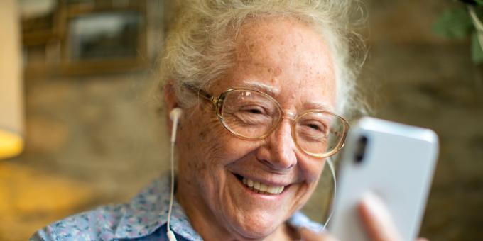 Ältere Frau nutzt Smartphone und Kopfhörer