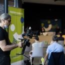 Kameramann stellt Stativ ein im Veranstaltungsraum.
