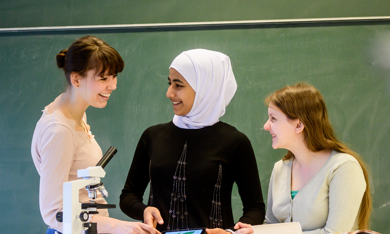 """DigiBitS Aktionstag """"Schule gegen Hate Speech"""" Eine Lehrerin mit Schüler:innen im Unterricht"""