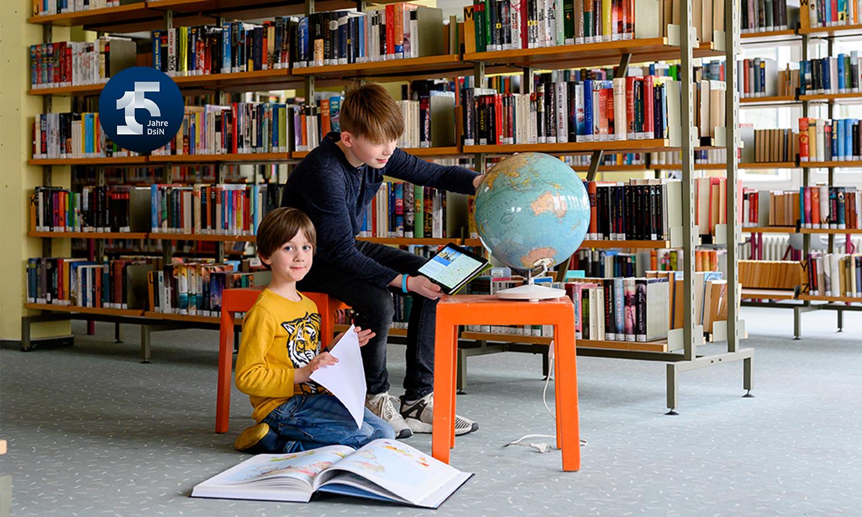 zwei Schüler lernen digital in einer Bibliothek mit DigiBitS, 15 Jahre DsiN