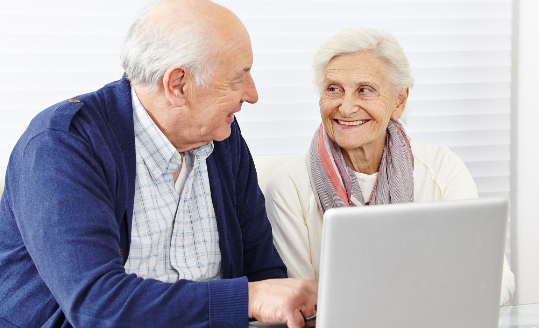 Zwei ältere Personen sitzen vor einem Notebook und lächeln sich an