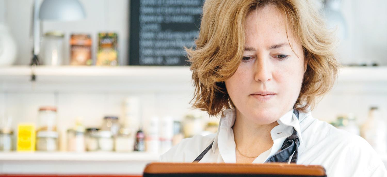 Ausschnitt des Titelbildes des DsiN-Praxisreport Mittelstand: Eine Frau abreitet an einem Tablet