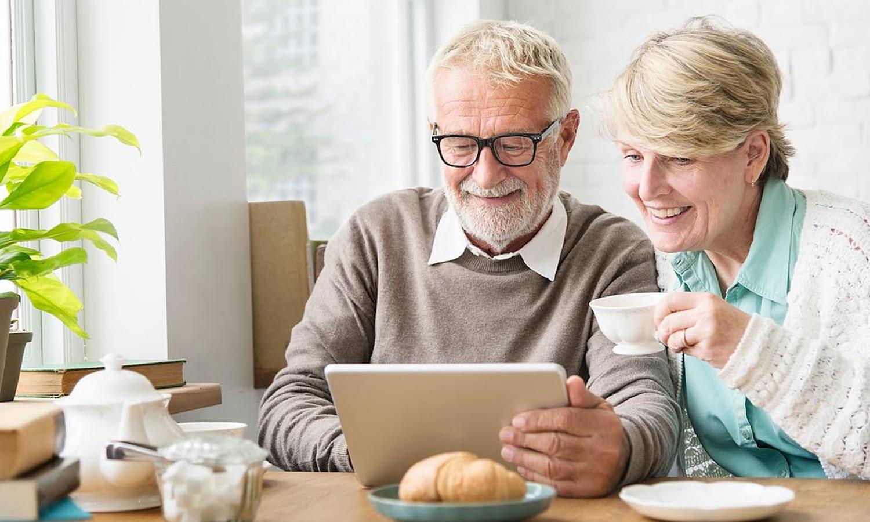 Senior und Seniorin am Online-Tablet beim Frühstück