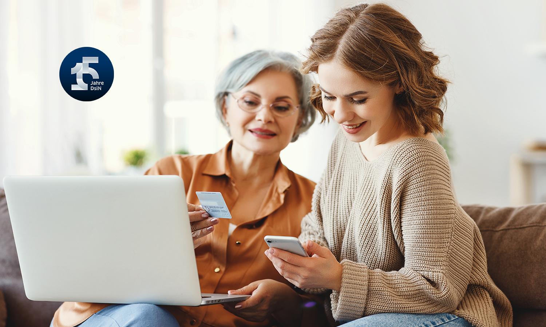 Ältere Frau und Tochter nutzen gemeinsam Laptop und Smartphone zur Verifizierung Ihrer Identität online, 15 Jahre DsiN