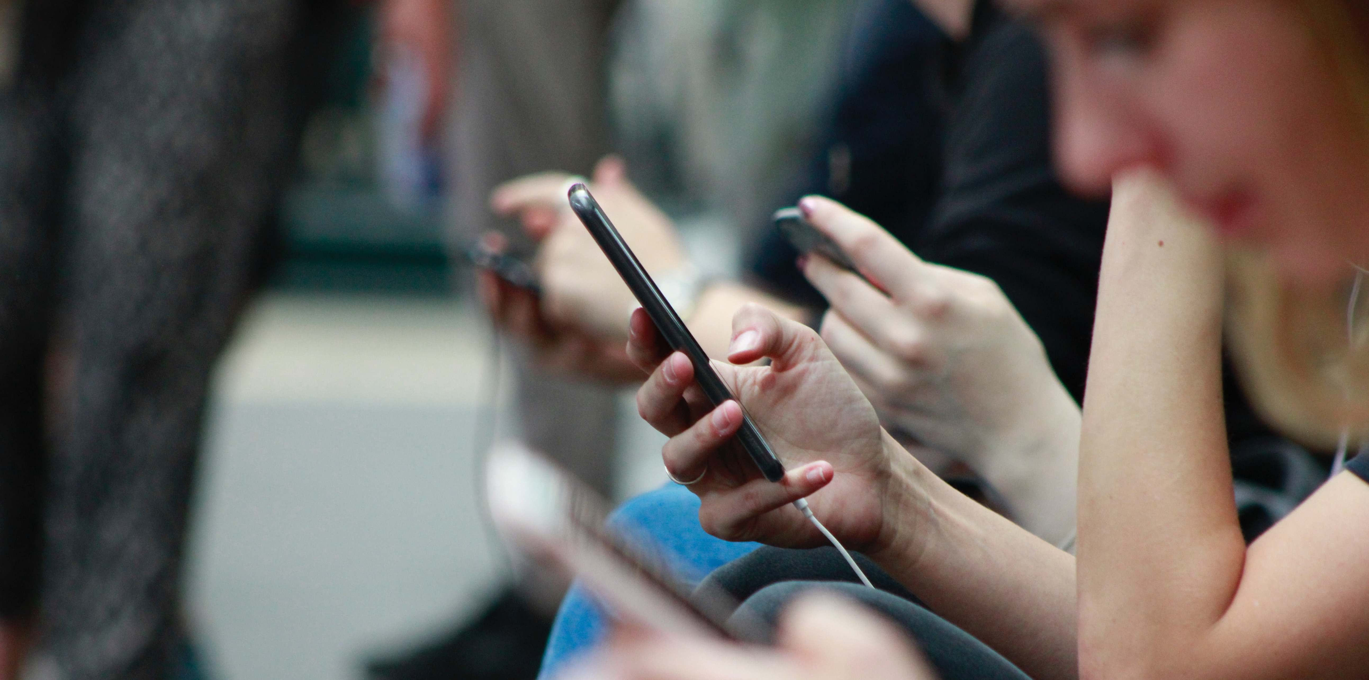 Frau liest auf dem Smartphone Stalkerware aufspüren und Smartphone-Spionage verhindern