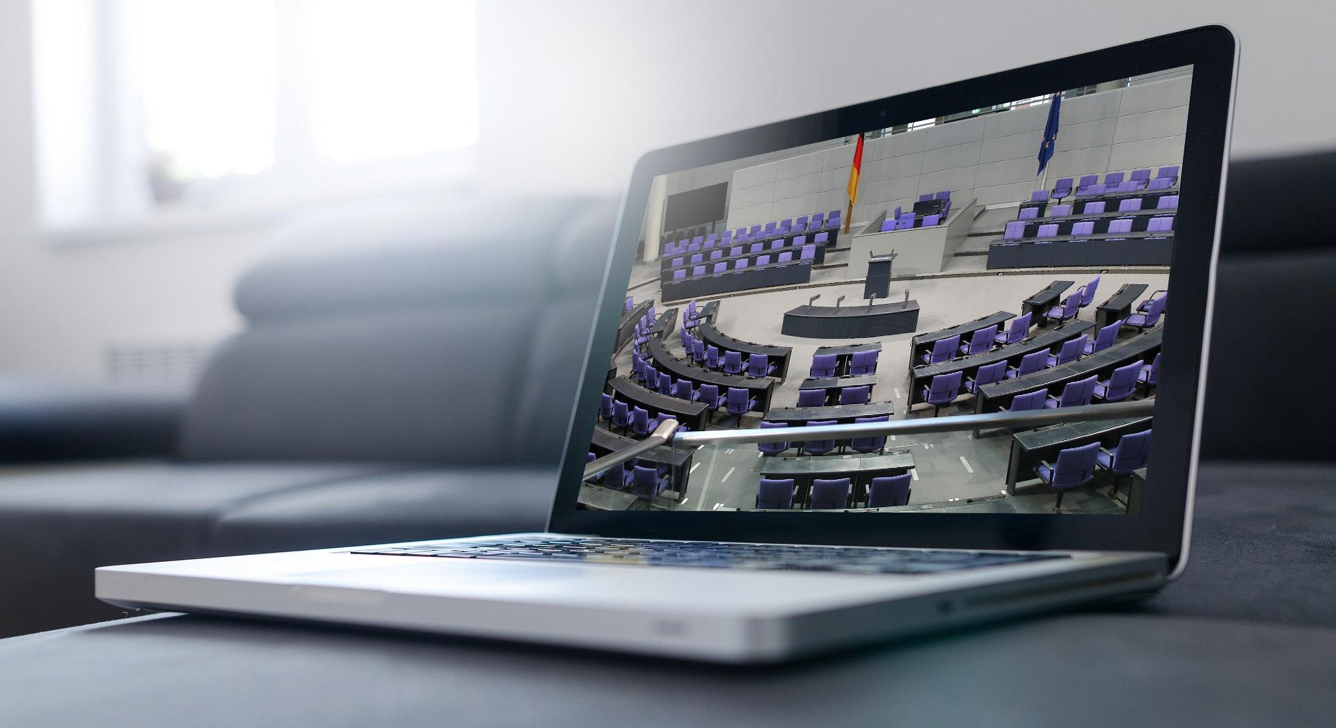 PolisiN bietet neue Workshops und Webinare für Politiker und Politikerinnen an. Bild: Aufgeklappter Laptop mit Bild des Bundestages